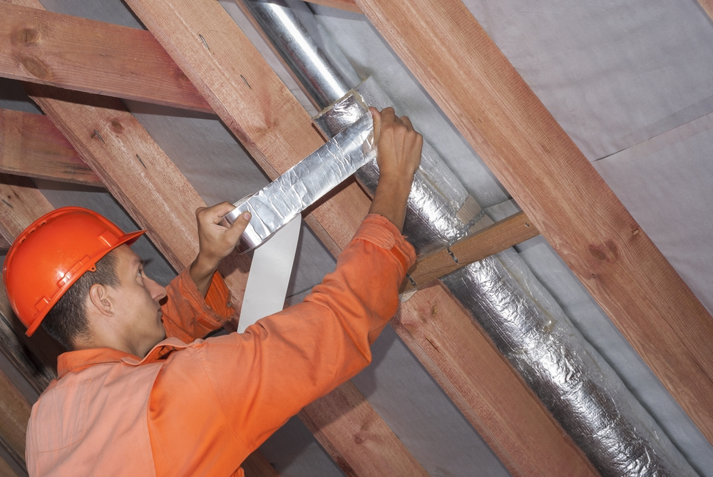 Man fixing duct in attic