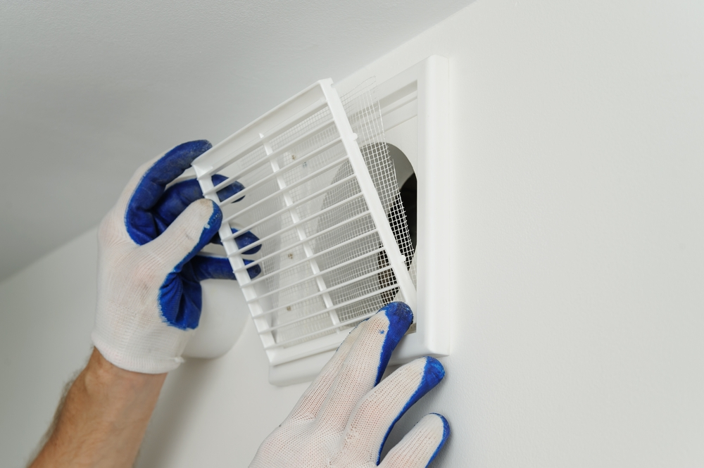 gloved hands manipulating an indoor air vent cover