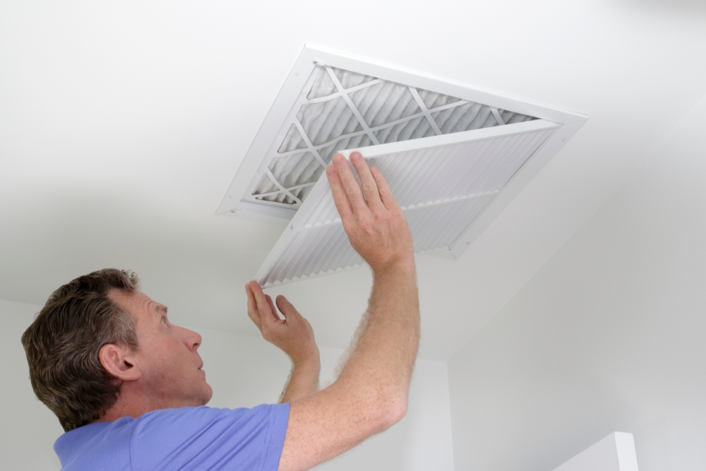 Man inspecting inside residential duct