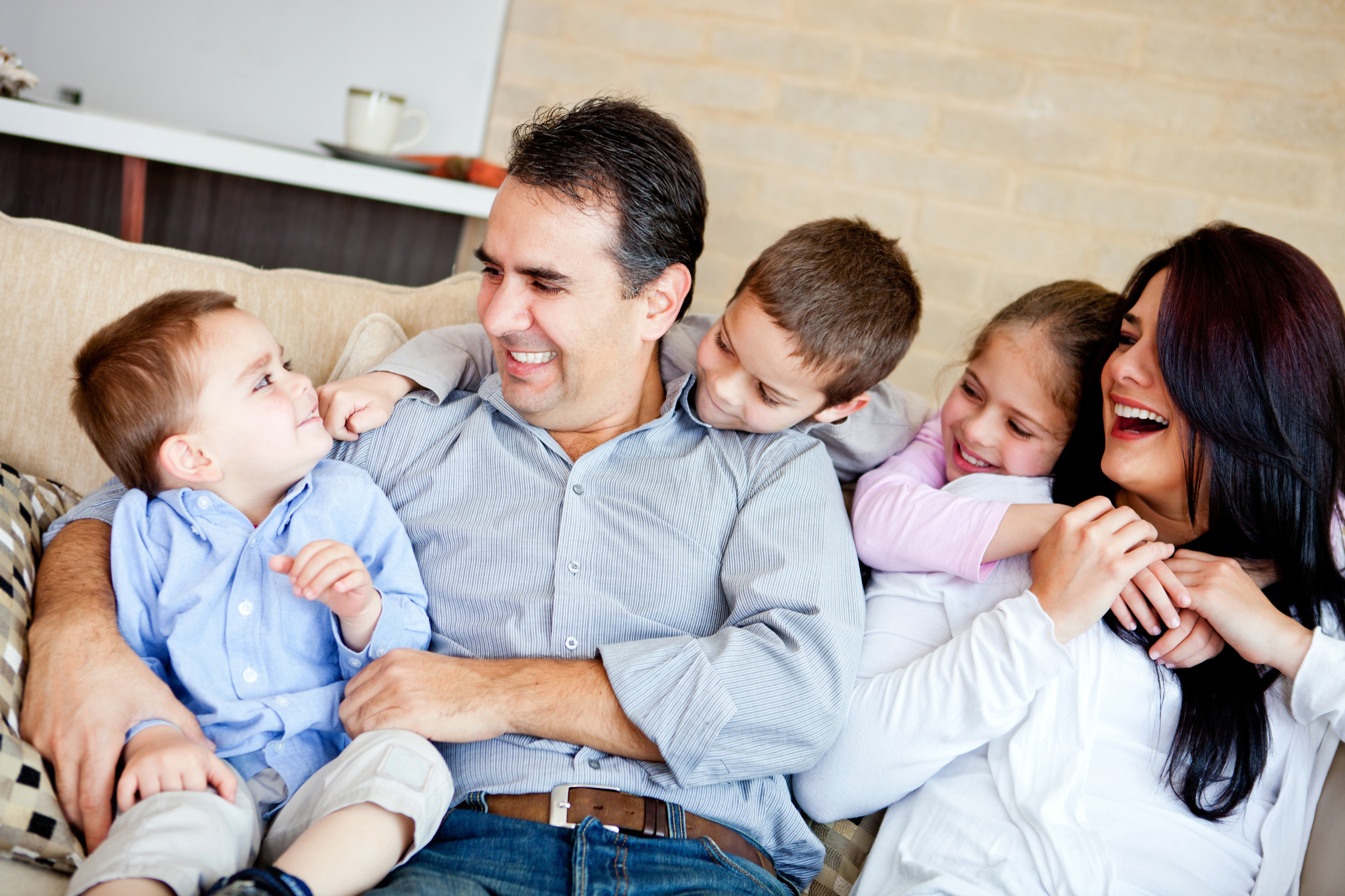 Happy and Comfortable Family Sitting Together on Couch