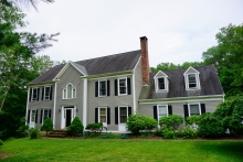 Large light gray home with white trim and manicured lawn
