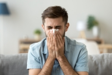man at home sneezing into tissue