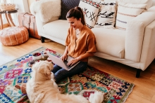 woman and her dog at home together on living room floor