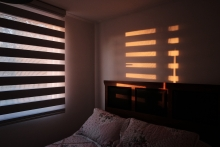 dark bedroom with sun rising through the shades
