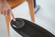 person turning on air purifier in home close up