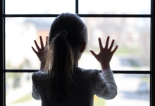 child against window of house
