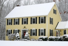 yellow two story classic colonial home during winter, christmas wreath front door