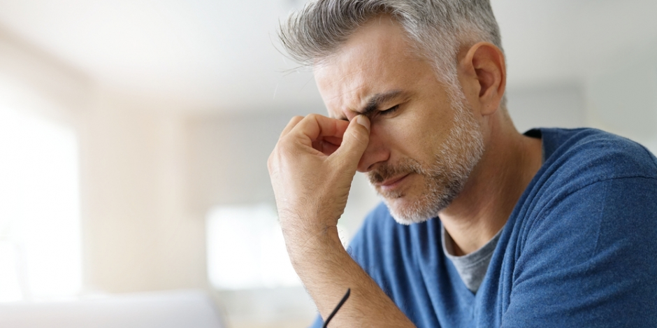man pinching nose in headache at home