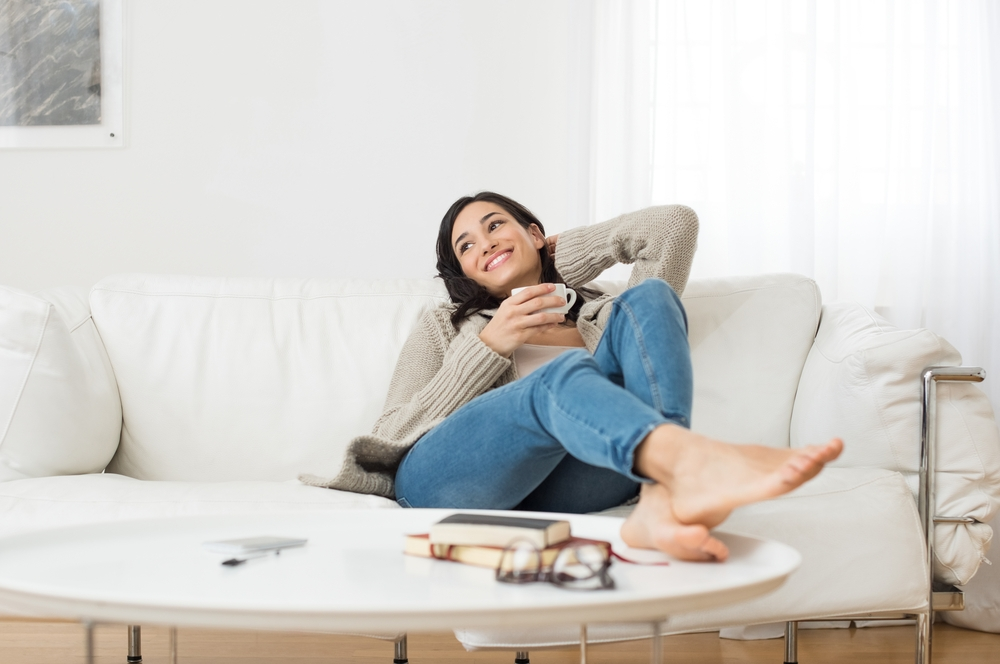 A woman sitting on a couch and breathing deeply